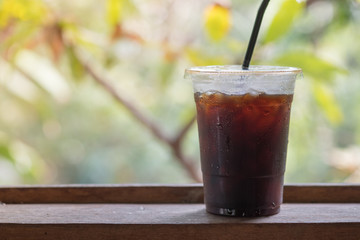 Close up of take away plastic cup of iced black coffee (Americano) with garden view.