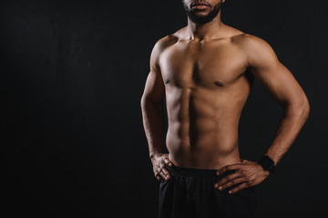 cropped shot of muscular shirtless african american man standing with hands on waist isolated on black