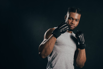 young african american kickboxer in gloves looking at camera isolated on black