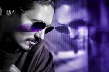 Handsome guy in sunglasses with reflection. Fashionable ultraviolet artistic image. Composite image with black and white. Color of the year.