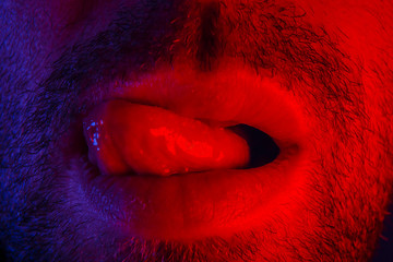 Macro close up on man with seductive facial expression sticking out his tongue licking his lips