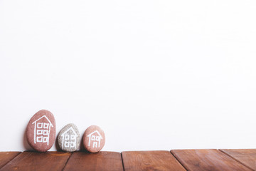 Three houses drawn on stones over brown wood and white background