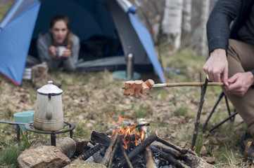 couple preparing dinner on campfire near camping tent during autumn cold season