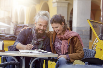 Woman and man smiling looking at map while seated at cafe.Front view. Caucasian couple in love roadtrip vacation italian travel on convertible car