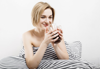 The girl drinks coffee in bed. Morning girl The young girl wakes up in the morning. Sleep. Morning awakening. Reading the press in bed. Under the blanket.