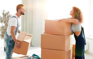 Young family unpacking boxes in a new house.