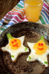 Fried eggs shaped as stars with funny faces in a pan