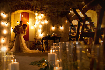 evening stylish wedding couple in rustic decorations and candles