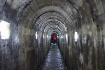 Person walking on illuminated tunnel