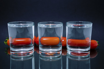 cherry tomatoes through three glasses with water on the glass