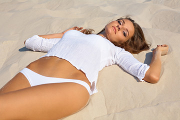 Young beautiful woman lies on the sea beach. Summer outdoor