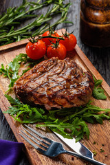 Grilled beef steak on wooden cutting board.