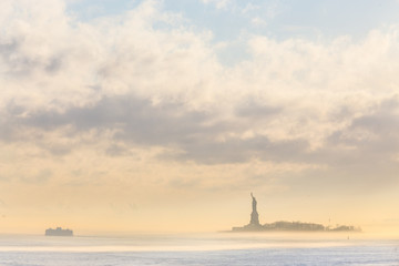 Staten Island Ferry cruises past the Statue of Liberty on a misty sunset. Manhattan, New York City, United States of America. Vertical composition. Copy space.