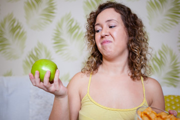 Curly woman holding an apple and grimace on face