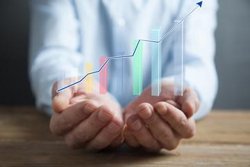 businessman holding a hand-drawn bar graph in his hand