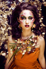 beauty woman with face art and jewelry from flowers orchids clos