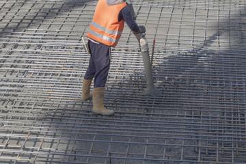 Lavoratori gettano cemento su un sito per  la costruzione di  un parcheggio interrato