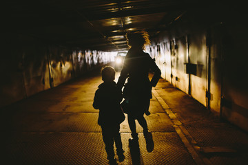 Woman and kid running away through tunnel