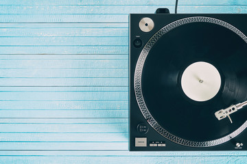 Turntable vinyl record player on the background blue wooden boards. Sound technology for DJ to mix & play music. Needle on a vinyl record. Black vinyl record