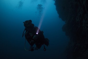 Scuba diver diving in the night with torch light