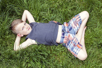 Six year old boy enjoys cool green grass on a warm spring day in shorts and sleeveless shirt