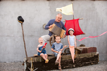 Three cute boys with father on pirate ship as sailors on summer evening. Children have fun outdoors. Happy kids on holiday in village. Home show with vintage boat and a white chicken. Adventures going