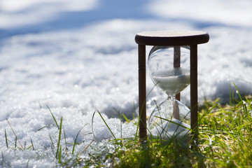 Hourglass as a symbol of changing of the seasons. Spring is coming.