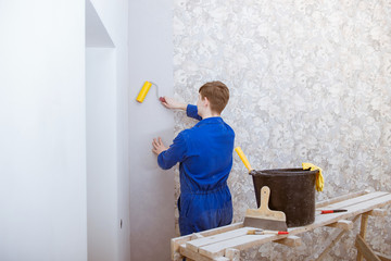 Young worker making repair in room, wallpapering on wall