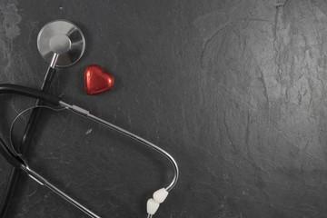 Stethoskop mit Herz auf Schiefer