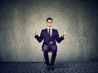 Young business man meditating on chair