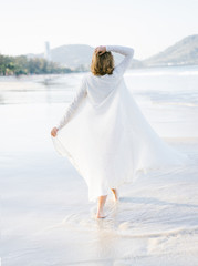 Female in long gown walking on beach