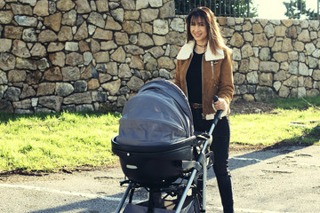 Beautiful young mother pushing a stroller in the park