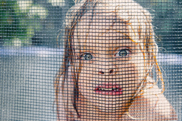 Boy face squished up against trampoline net