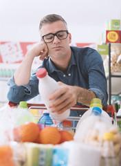 Sad man doing grocery shopping