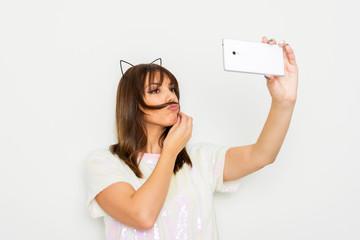 Young woman making hair mustache having fun taking a selfie