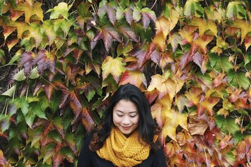 Smiling girl against very colourful leafy wall