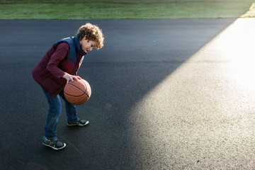 Young boy bounces a basketball on an outdoor court