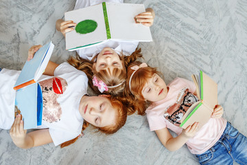 A group of children lays on the floor and reads books. The concept of lifestyle, childhood, education, family, school.