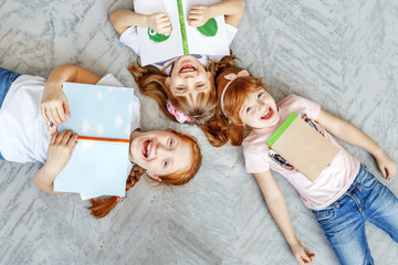 Three happy children lie on the floor and read books. The concept of lifestyle, childhood, education, family, school.