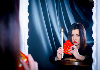 A woman with tarot cards and a candle looks into her reflection in the mirror. Prediction of the future, fortune telling.