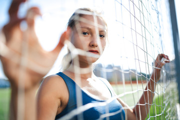 Beautiful girl in a blue shirt in leggings is on the football field is kept behind the net from the gate. Editorial sport concept