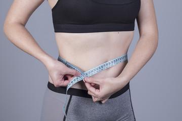 Mujer midiendo la cintura con cinta metrica