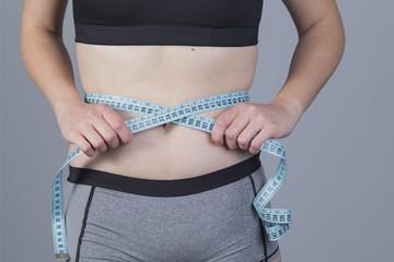 Mujer midiendo la cintura con cinta métrica