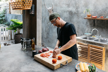 Male chopping tomatoes for preparing food in taco dinner meal in trendy kitchen interior