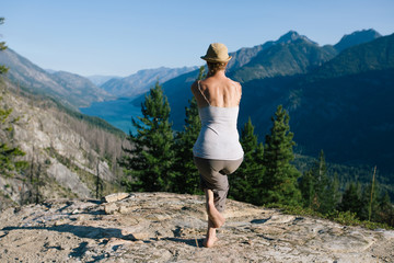 Young woman on rock looking at a lake below