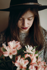 stylish hipster girl in hat holding pink flowers in room. boho woman in stylish clothes holding beautiful alstroemeria in hands in spring morning. sensual female portrait.