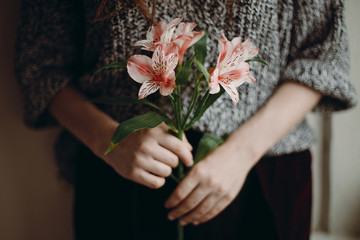 stylish hipster girl holding pink flowers. boho woman with beautiful alstroemeria in hands. close up. creative sensual spring image