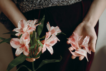 stylish hipster girl holding pink flowers and petals. boho woman with beautiful alstroemeria in hands. close up. creative sensual spring image. eco. save and protect