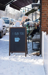 "City street cafe has a fun drawing of a cup of hot drink and the words ""I own you"". It`s sunny day. Pleasant atmosphere of a winter sunny day or morning. Around there are people and white snow."