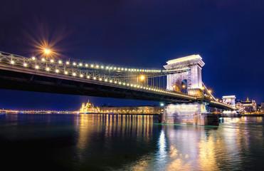 Night view of illuminated Budapest with Danube river, parliament,  and chain bridge, Hungary.